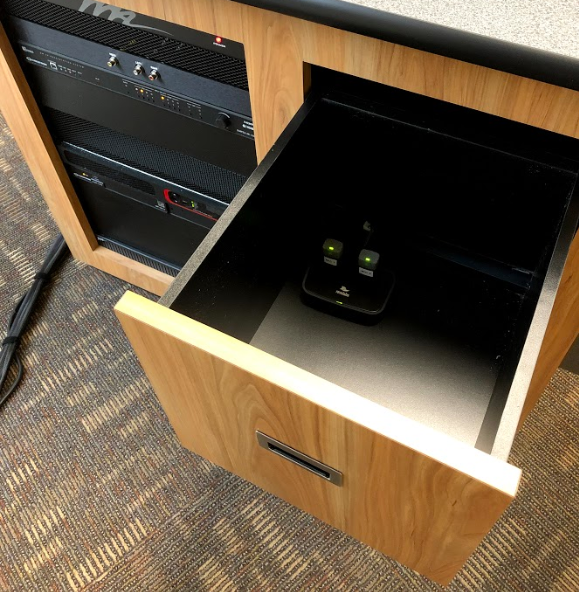 Photo of open drawer with microphones in charging station